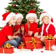 Christmas kids in Santa hat with presents gift boxes — Stock Photo