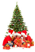 Christmas kids in red Santa hat opening gift box under fir over white background — Stock Photo