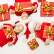 Christmas helpers kids with red presents gift box in Santa hat — Zdjęcie stockowe