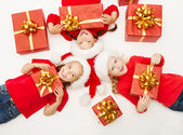 Christmas helpers kids with red presents gift box in Santa hat — Stock Photo