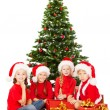 Stock Photo: Christmas kids in Santhat with presents sitting under fir tre
