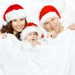 Christmas family and baby in Santa Claus hat lying in white background — Stock Photo