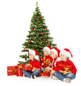 Christmas helpers kids in Santa hat with presents sitting under fir tre — Stock Photo