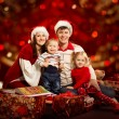 Christmas family of four persons happy smiling over red backgroud — Stock Photo #35233201