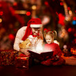 Christmas family reading book. Father and child opening magic fairy tal — Stock Photo