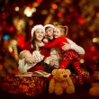 Christmas family of four persons happy smiling over red backgroud — Stok fotoğraf