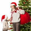 Christmas  helper grandson, Santa Claus grandfather with red bag in front fir tree — Stock Photo