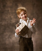Child holding gift box. Vintage style. — Stock Photo