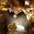 Stock Photo: Child opening birthday present box. Magic shining gift.