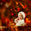 Christmas baby in Santa hat holding red ball near present gift box — Foto Stock