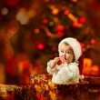 Christmas baby in Santa hat holding red ball near present gift box — Stok fotoğraf
