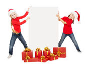 Happy Christmas kids holding banner. Santa helpers in caps with — Stock Photo
