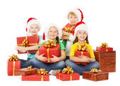 Happy Christmas kids holding presents. Santa helpers with gifts. — Stock Photo
