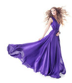 Woman in purple silk fluttering waving dress walking over white background — Stock Photo