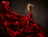 Woman in red waving dress with flying fabric. Back side view — Stock Photo