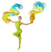 Woman dancing with flying colorful fabric, white background — Stock Photo