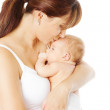 Mother kissing newborn baby holding in hand, white background — Stock Photo