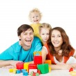 Happy family four persons. Smiling parents kids playing toys blocks — Stock Photo