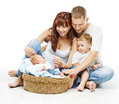 Young family four persons, smiling father mother and two children newborn sons — Stock Photo