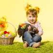 Easter little girl, kid holding bunny rabbit basket eggs over yellow background — Stock Photo