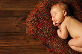 Baby newborn portrait, kid sleeping in woolen blanket on brown wooden background — Stock Photo