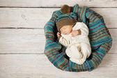 Baby newborn sleeping in woolen hat on white wooden background, warm winter country style — Stock Photo