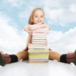 School girl and books stack. Smiling happy child pupil sitting over blue cloudy sky. — Stock Photo #43841319