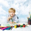 Child painting with color brush using a lot of drawing tools. Happy creative kid artist over blue sky. Creativity and inspiration concept. — Stock Photo #43841323