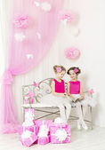Birthday party happy kids with presents. Girl sisters consider congratulation album next to pink gift boxes — Stock Photo