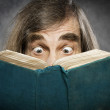 Senior reading open book, surprised old man, amazing eyes looking blank cover — Stock Photo #47256977