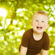 Happy child smiling over green background. Close up baby portrait. — Stock Photo