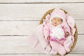 Baby girl with gift sleeping on wooden background, newborn in basket with present. Birthday party invitation card — Stok fotoğraf
