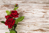 Rose flowers, red on wooden grunge background, floral card copy space — Stok fotoğraf