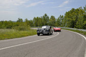 Black Jaguar and red Maserati during 1000 Miglia — Stock Photo