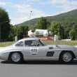Постер, плакат: A silver gray Mercedes 300 SL W Gullwing drives before the 1000 Miglia monument during the 1000 Miglia classic car race on May 15 2014 in Brescia This car was built in 1956