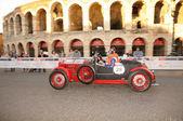 A red and black Lancia Lambda VII drives before the Arena di Verona during the 1000 Miglia classic car race on May 15, 2014 in Verona. This car was built in 1927 — Stock Photo