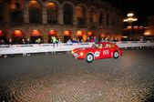 A red Ermini 1100 Berlinetta drives before the Arena di Verona during the 1000 Miglia classic car race on May 15, 2014 in Verona. This car was built in 1950 — Stock Photo