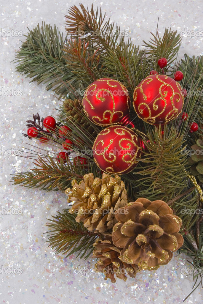 Christmas tree branch with pine cones, ornaments and snow — Stock Photo #13760402