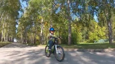 Young boy riding bicycle on a autumn day — Stock video
