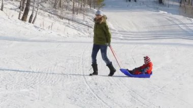 Happy woman pulling sledge with her kid from the snowy hill — Stock Video
