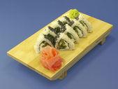 Rotoli di sushi su piastra di legno — Foto Stock