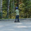 Six years old boy learning to ride on rollerblades — Stock Video