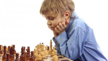 Boy thinking and looking at the chess board — Stock Video