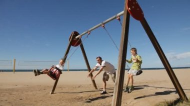 Boys swinging on a swing with dad — Vídeo de stock