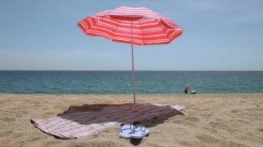 Mat and flip flops under a beach umbrella — Stok video