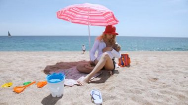 Woman with baby under umbrella on beach — Stock Video