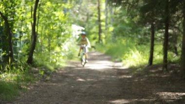 Liten pojke i en hjälm som rider på en cykel. — Stockvideo