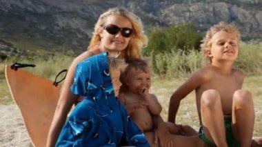 湖の海岸で休む彼女の 3 人の子供を持つ女性 — ストックビデオ