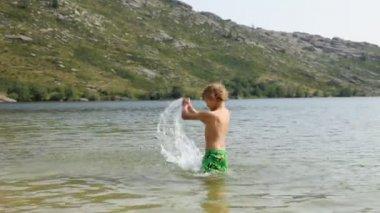 Boy making splashes in the mountain lake — Stock Video