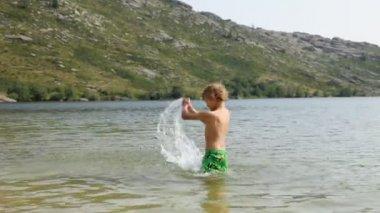 Jongen spatten maken in het bergmeer — Stockvideo